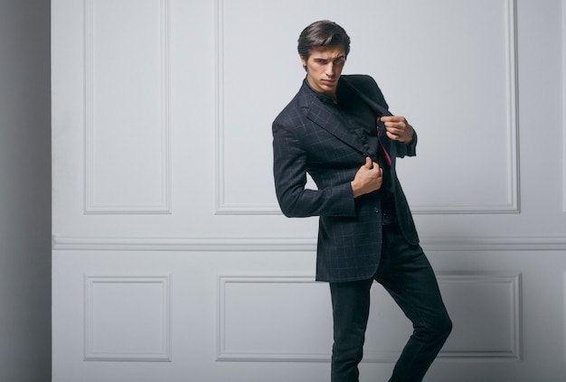 Деловой человек носит черный элегантный портрет костюма на фоне неоклассической стены. портрет крупного плана красивого мужчины. горизонтальный вид.
