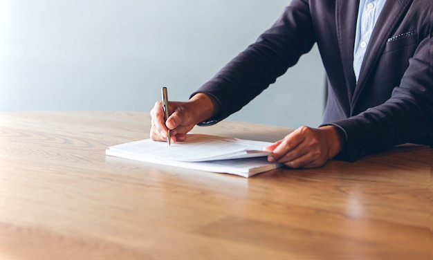 Business man wear  black suit use pen to signing contract documents on a wooden desk in the office