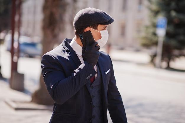 ビジネスの男性は、スーツと医療フェイスマスクとキャップを着用、電話で話します。 mers-cov、新規コロナウイルス2019-ncov