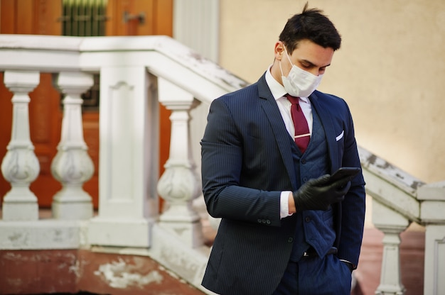 ビジネスの男性は、医療用フェイスマスクと携帯電話を手にスーツに着用します。 mers-cov、新規コロナウイルス2019-ncov