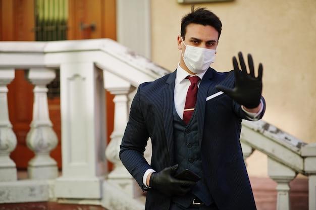 ビジネスの男性は、医療用マスクと携帯電話を手に一時停止の標識を示すスーツを着ます。 mers-cov、新規コロナウイルス2019-ncov