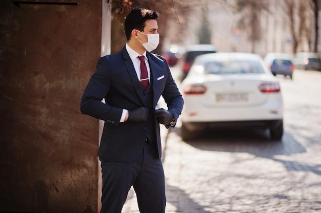 ビジネスの男性は、医療用フェイスマスクとスーツを着ます。 mers-cov、新規コロナウイルス2019-ncov