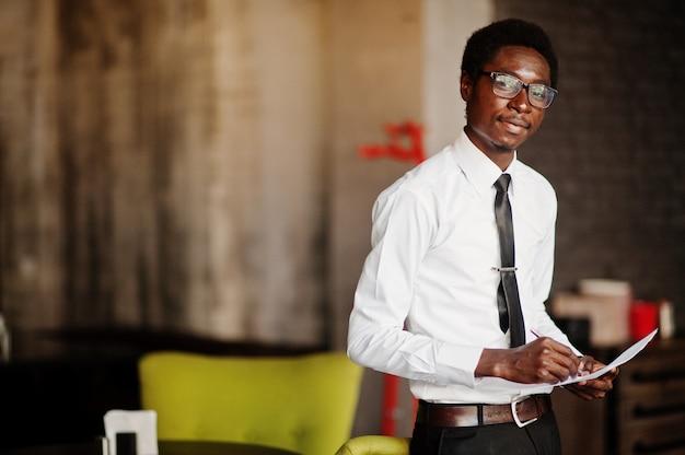 Деловой человек носить на белой рубашке, галстуке и очках в офисе, держа бумаги на руках и написать что-то