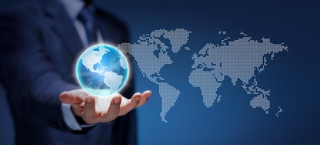 ビジネスマンのウェアスーツは、ブループラネットアースを保持します。ビジネスマンの手にあるグローバルビジネスの世界は、世界的なビジネス、世界地図、接続ネットワーク、インターネット技術、環境、ロジスティックコンセプトを示しています。