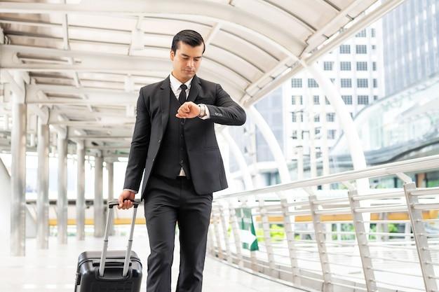 Деловой человек в костюме с чемоданом, несущий багаж, у него было озабоченное лицо, он шел в спешке и смотрел на часы на ходу - концепция образа жизни деловых людей