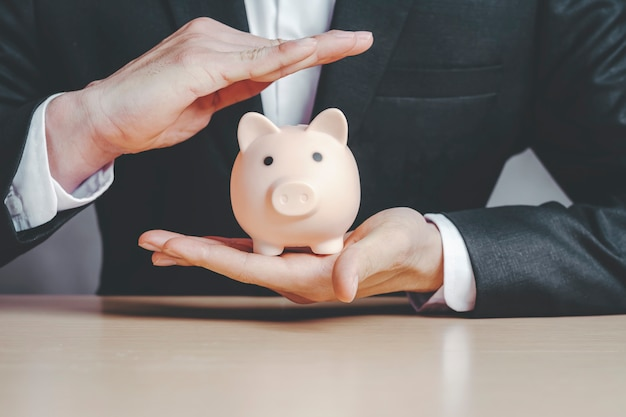 Business man wearing a black suit and insurance to protect the piggy bank in the hand concepts of life insurance.