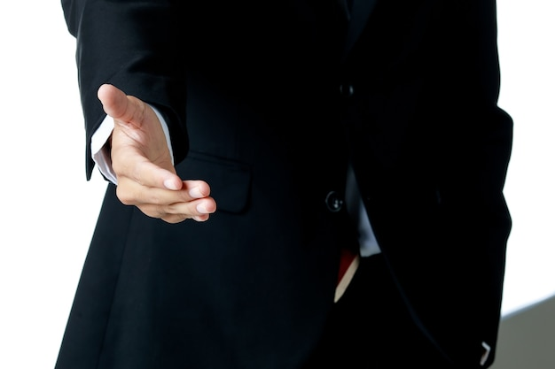 白いシャツとネクタイと黒のスーツを着ているビジネスマンは、白い背景で手を振るために片手を出します。孤立