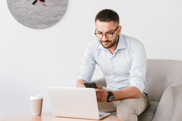 안락의 자에 앉아 안경을 착용하고 사무실 내부에서 노트북에서 작업하는 동안 스마트 폰을 사용하는 비지니스 맨
