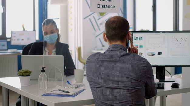 Business man wearing face mask talking at phone while sitting at desk in company office during coronavirus global pandemic. coworkers keeping social distancing to avoid virus disease