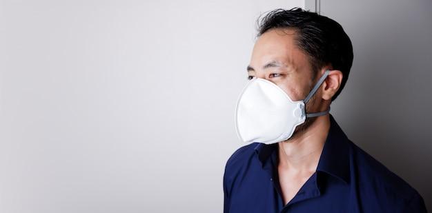 Pm2.5大気汚染、二酸化炭素、ウイルスインフルエンザのため、白い背景にn95またはフェイスマスクを身に着けているビジネスマン。