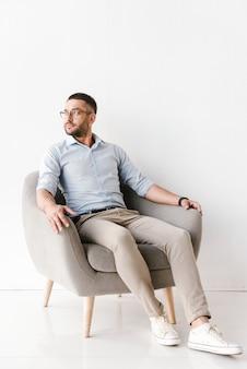 안락의 자에 앉아 옆으로 찾고 세련된 공식적인 옷을 입고 비즈니스 남자는 흰색에 고립