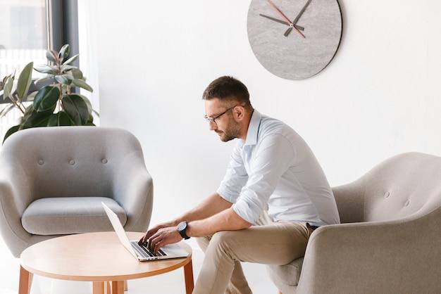 안락의 자에 앉아 사무실 인테리어에 노트북에서 일하는 세련된 공식적인 옷을 입고 비즈니스 남자
