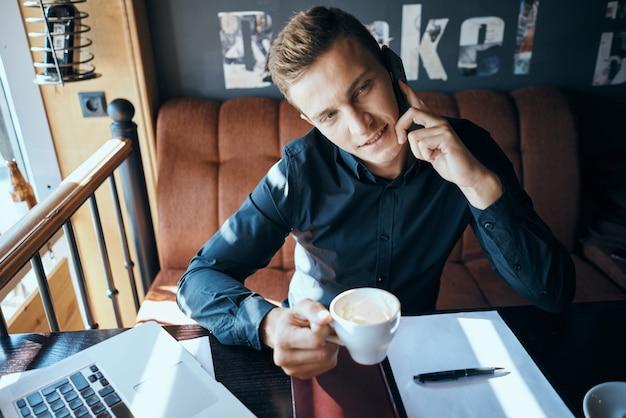 カフェの感情でコーヒーのカップを持つビジネス男がオフィスストレスイライラディレクターで働く