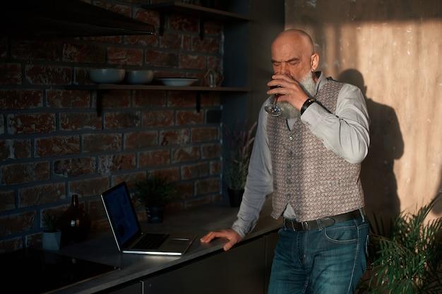 彼のラップトップの画面を見ているワインのグラスを持つビジネスマン