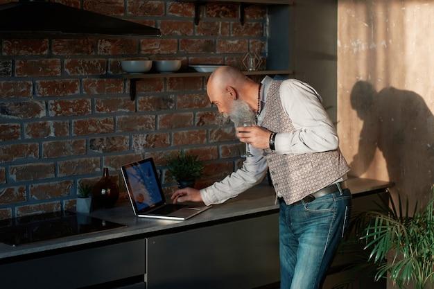 彼の自宅のキッチンでラップトップを使用してワインのグラスを持つビジネスマン