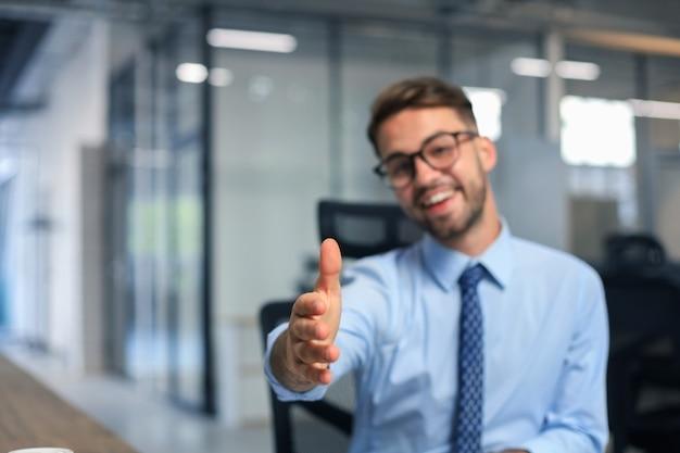 オフィスで契約を結ぶ準備ができている開いた手を持つビジネスマン。