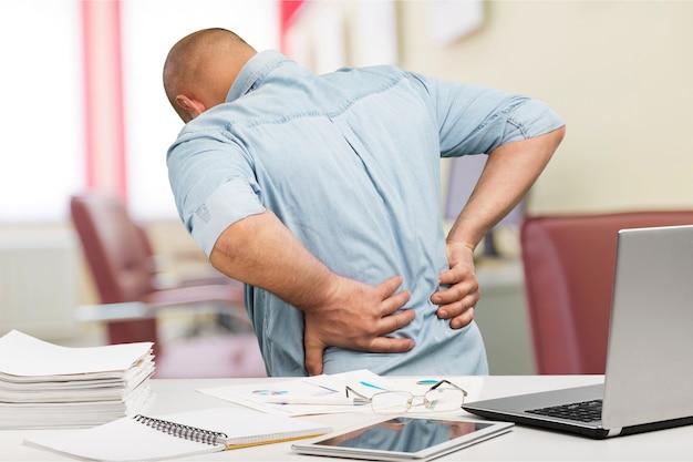 Деловой человек с болями в спине в офисе