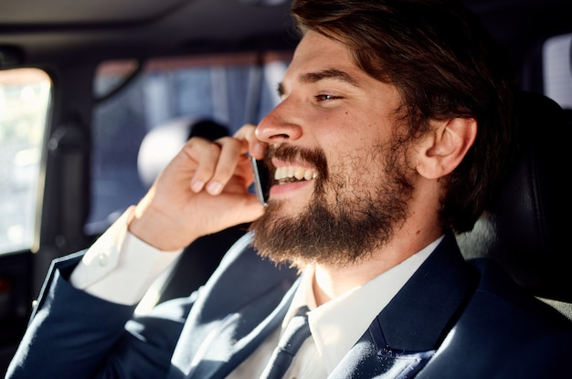 Business man with a beard talking on the phone in a car trip