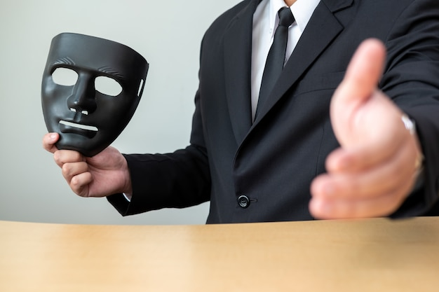 A business man with a black mask covering the insincerity of doing business together.