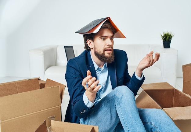 상자와 비즈니스 남자는 물건을 풀고 사무실 바닥에 앉아있다.