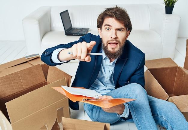 상자와 비즈니스 남자는 물건을 풀고 사무실 바닥에 앉아