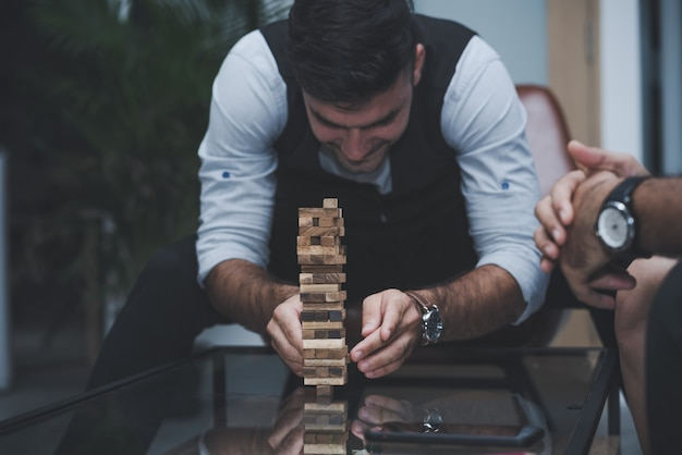 Business man with colleagues relaxing play wood blocks stacks game together in office