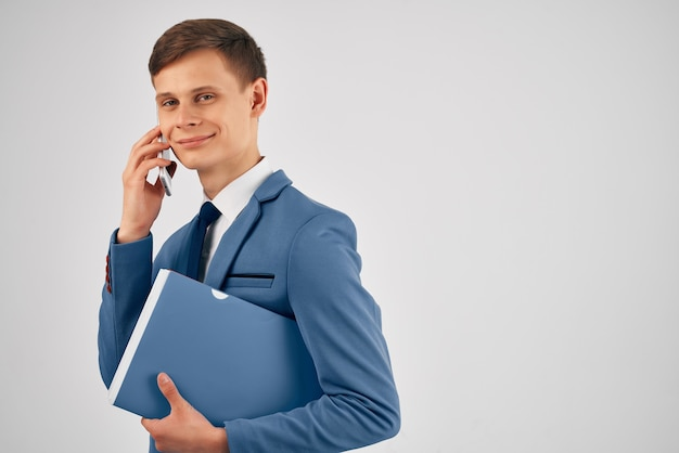 Business man with documents in a suit talking on the phone office work