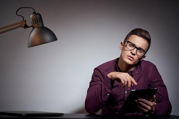 Деловой человек в очках и рубашке, сидя за столом