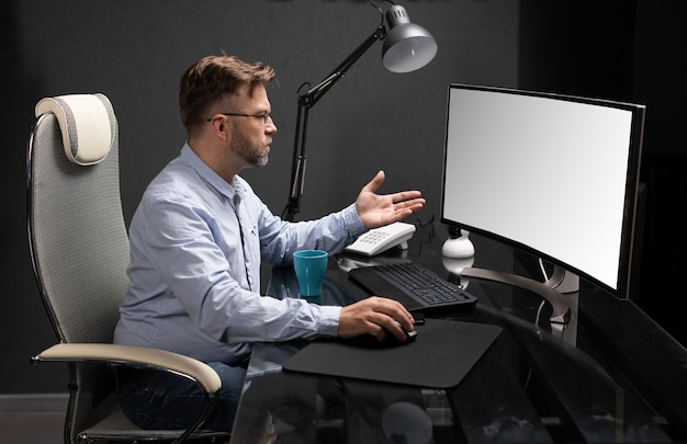 Business man with glasses working in office at computer table and drinking coffee from bright cup