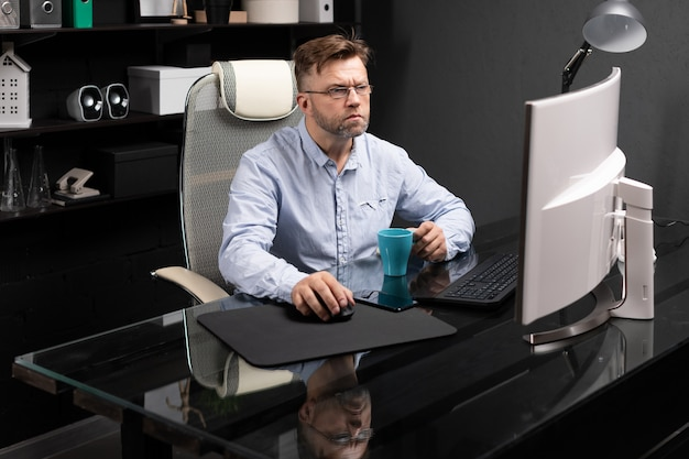 Business man with glasses working in the office at the computer table and drinking coffee from a small cup