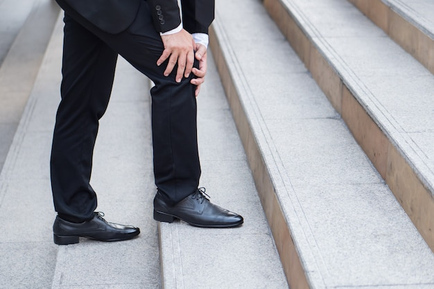 Business man with knee pain obstacle concept