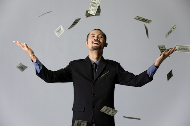 Деловой человек с деньгами на сером фоне