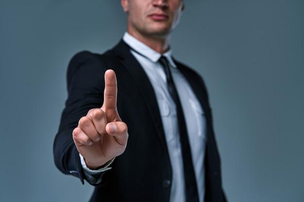 何かを指している、または灰色の背景のタッチスクリーンに触れているビジネスマン。