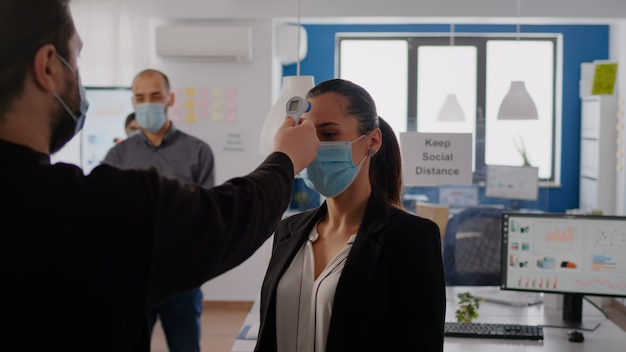 保護フェイスマスクをチェックしているビジネスマンは、ウイルス感染を防ぐために赤外線温度計を使用して同僚の体温をチェックしています。コロナウイルスの蔓延を防ぐために社会的距離を保つ同僚
