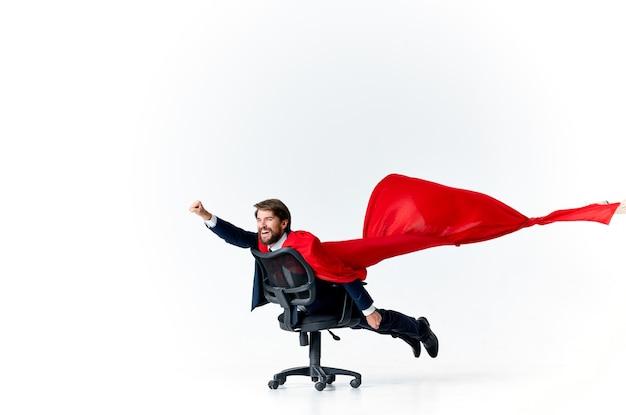 椅子のヒーローのスーパーマンに赤いマントを着たビジネスマン。高品質の写真