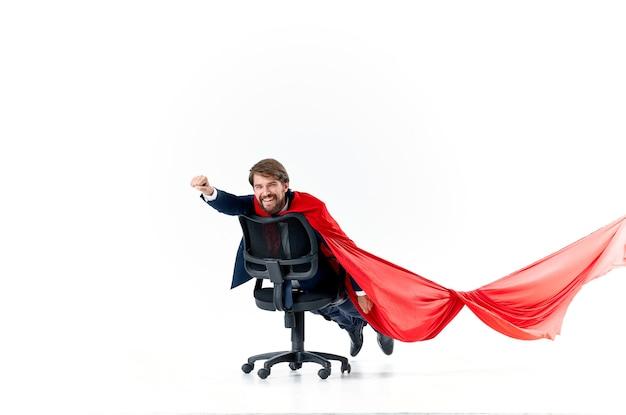 椅子のヒーローのスーパーマンに赤いマントを着たビジネスマン