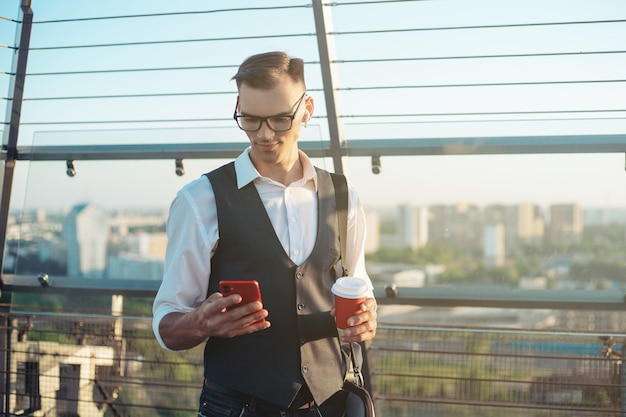Business man with a smartphone and a takeaway coffee standing on
