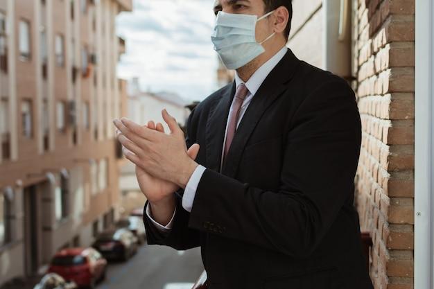 日没時にテラスからコロナウイルス(covid19)と戦っている人々を称賛するスーツ、ネクタイ、マスクを持つビジネスマン