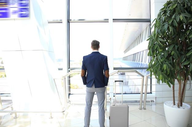 공항 홀에 가방을 들고 있는 사업가.