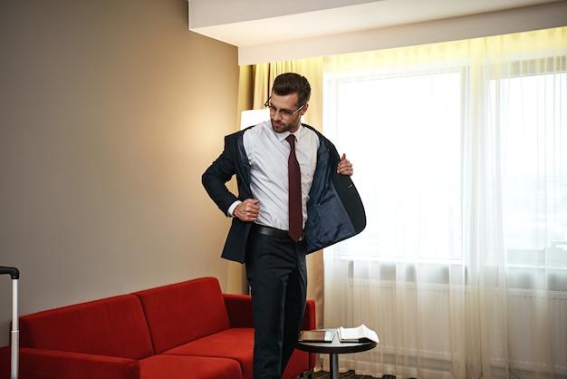 Деловой человек с чемоданом снимает куртку возле дивана в гостиничном номере
