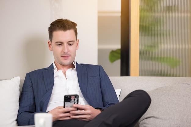 Деловой человек с чемоданом с помощью приложения для смартфона сидит на диване