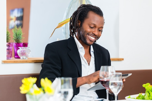Business man with tablet in restaurant