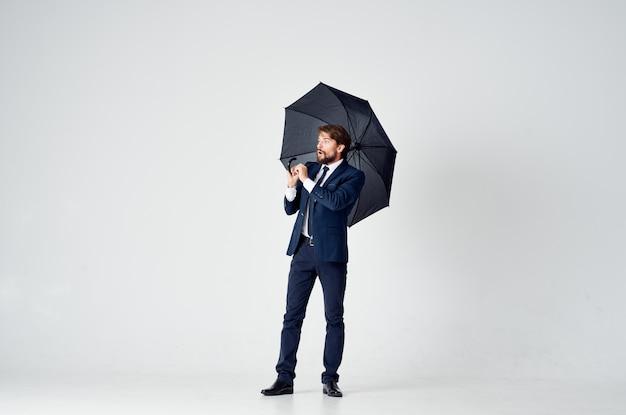 雨の悪天候スタジオから手を保護する傘を持つビジネスマン