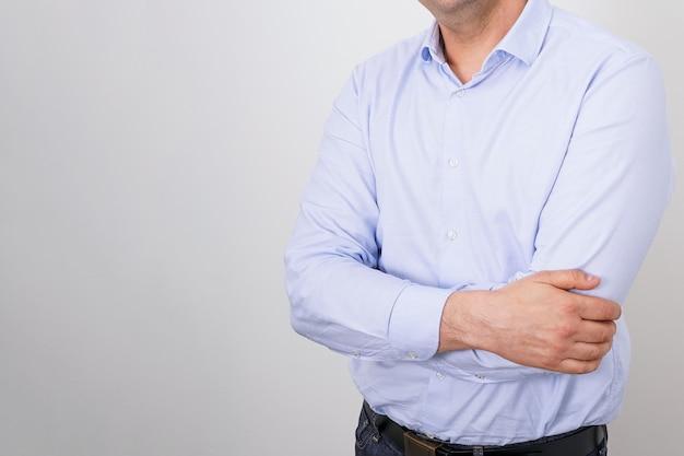 밝은 배경에 접힌 손으로 파란 셔츠에 얼굴이 없는 사업가