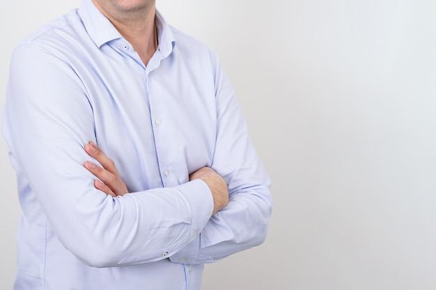 가벼운 벽에 접힌 손으로 파란색 셔츠에 얼굴이없는 비즈니스 남자, 자신감 비즈니스 남자의 개념