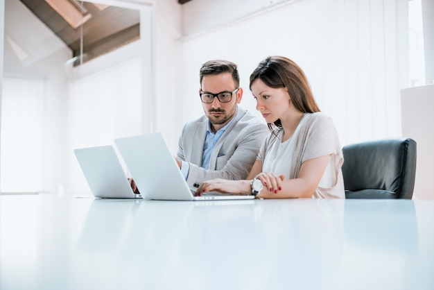Business man and woman colleagues sitting with laptops on desk in office