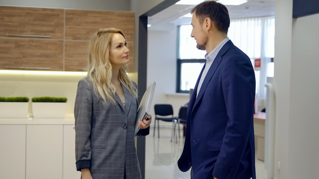 Business man and woman discussing a new agreement in the office.