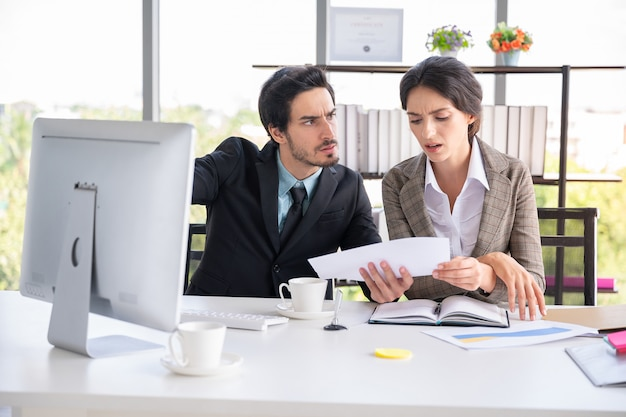 Business man and woman looking  paper document in office