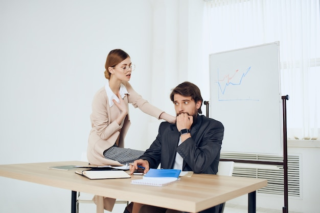 Business man and woman sitting at the table working office officials