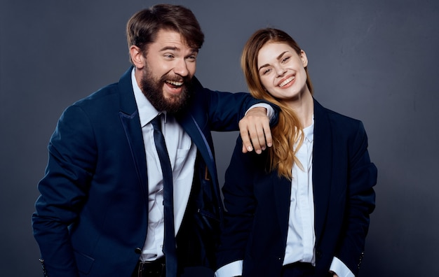Business man and woman in suit gesturing with hands on gray background cropped view